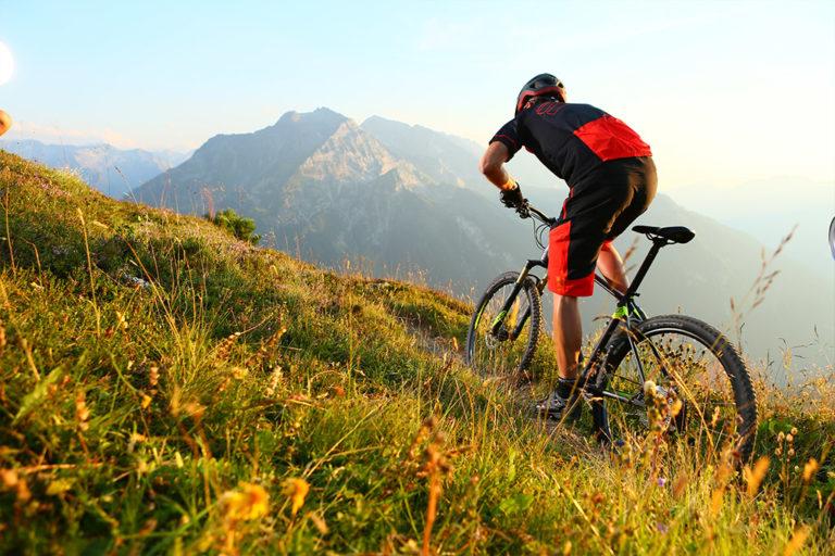 Mann fährt auf Fahrrad eine steile Wiese hoch
