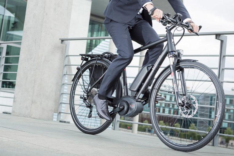 Mann in Anzug fährt Fahrrad