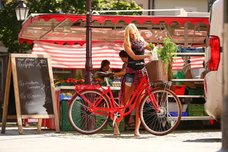 Marktstand mit Frau und Fahrrad, Fahrradkorb